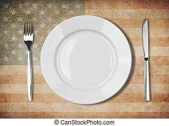 Plate, fork and knife on old USA flag