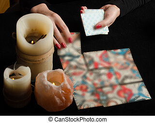 Hands of girl with divination cards on black background