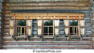 old russian wooden house with decorated windows - fragment...