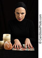 young woman with divination cards on black background