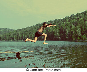 boy jumping in lake - vintage retro style - boy jumping in...
