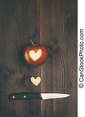 Apple with a heart cut into it - apple in close up with...