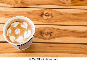 Coffee with heart pattern on wooden background