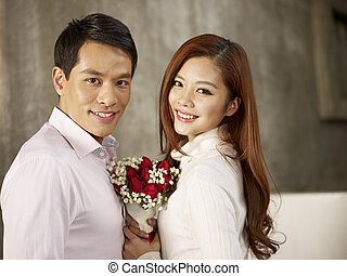 young man and woman in love - portrait of happy asian young...