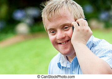 Handicapped boy talking on cell phone. - Close up portrait...