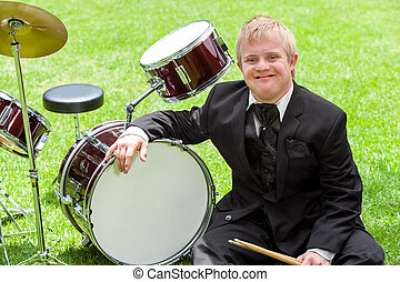 Young handicapped drummer next to drums. - Portrait of young...