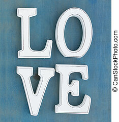 Love sign - White letters Love on blue wooden background