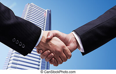 business deal - handshake on  background of skyscraper