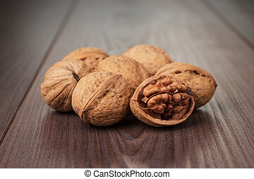 walnuts on the brown wooden table - three walnuts on the...