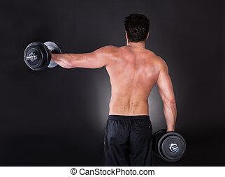 Man Exercising Dumbbells - Young Muscular Man Exercising...