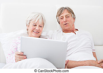 Senior Couple On Bed Looking At Laptop - Portrait Of Happy...