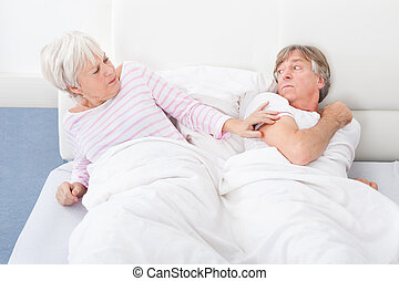 Angry Couple Lying On Bed