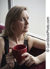 Blonde Woman with Red Coffee Cup Sitting by a Window -...