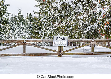 Winter Road Closed to traffic by a wooden barricade