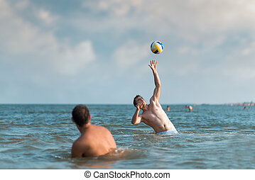 boys playing with a ball in water