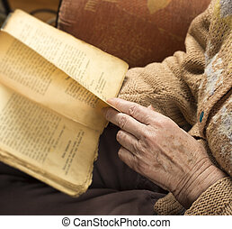Hands of an older woman reading book and relaxing