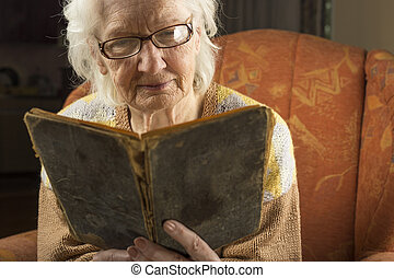 Older woman reading book close up