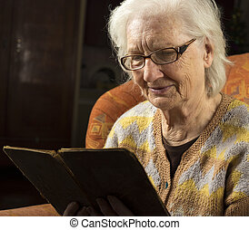 Portrait of an older woman reading book