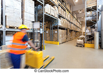 Forklift operator - Man pushing a yellow forklift in huge...
