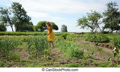 girl hoe grub weeds - Barefoot gardener girl in yellow dress...