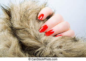 woman's hand with red long nails holding a fur