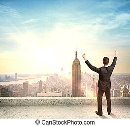happy businessman standing on roof and city on back