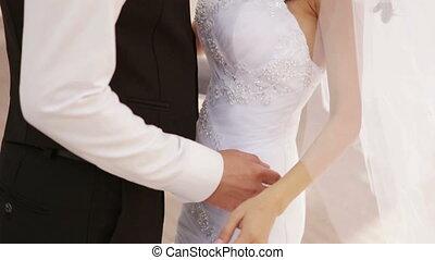 Groom hugs bride - A groom hugs fiancee for a waist and...