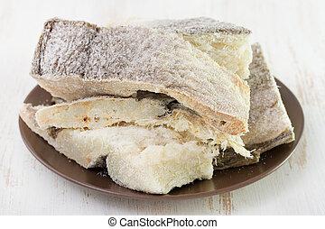 dry codfish on dark plate