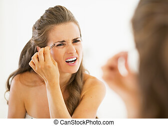 Displeased young woman tweezing eyebrows
