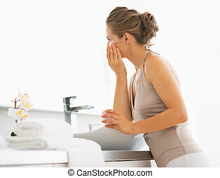 Young woman applying cream in bathroom