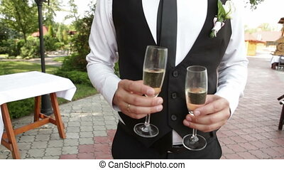 Groom carries champagne - A groom carries champagne Two...