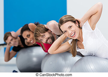 Group of friends doing Pilates at the gym balancing on the...