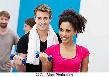 Multiethnic couple working out with dumbbells - Attractive...