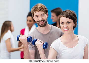Young couple working out at the gym - Attractive happy...