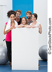 Happy fitness enthusiasts with a blank card - Happy fitness...