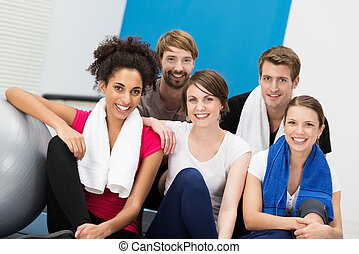 Happy group of young friends at the gym posing together for...