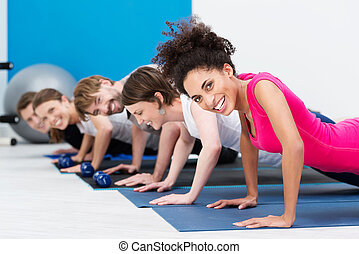 Group of fit young people doing push ups while working out...