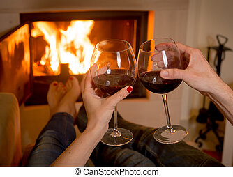 couple drinking wine in front of a fire - close up of young...