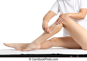 Beautician waxing a beautiful smooth woman legs with a wax strip isolated on a white background