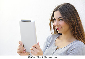 Pretty woman holding a tablet and looking at camera