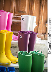some colored gum boots standing on stairs.