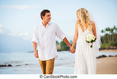 Married couple, bride and groom holding hands at sunset on beautiful tropical beach in Hawaii