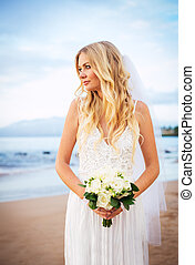 Beautiful bride in wedding dress with flowers at sunset on...