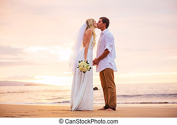 Married couple, bride and groom, kissing at sunset on...