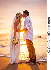 Married couple, bride and groom, kissing at sunset on beautiful tropical beach in Hawaii