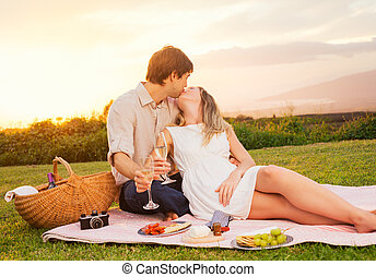 Couple Enjoying Romantic Sunset Picnic - Attractive Couple...