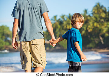 Happy father and son walking together on the beach, carefree...