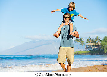 Happy father and son playing on tropical beach, carefree...