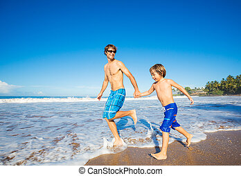 Happy father and son walking together at beach - Happy...