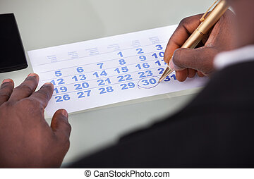 Businessman Marking On Calendar - Close-up Of Businessman...
